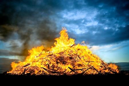 guy fawkes night: madera enorme hoguera ardiente alimentada al atardecer