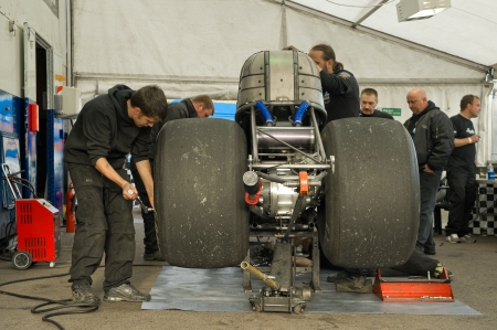 Santa Pod Raceway, UK - Oct 29, 2011: Mechanics working on a dragster at the Flame and Thunder racing event. Stock Photo - 11100432