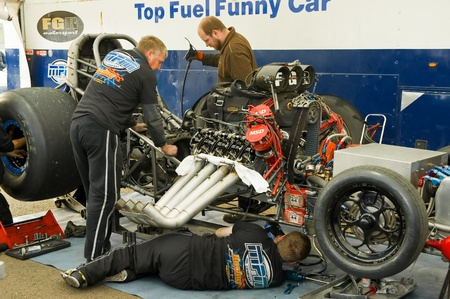 Santa Pod Raceway, UK - Oct 29, 2011: Mechanics working on a top fuel funny car at the Flame and Thunder drag-racing event. Stock Photo - 11117860