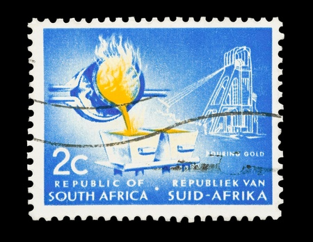 gold mine: Mail stamp printed in South Africa featuring gold mining and ingot production, circa 1961 Stock Photo
