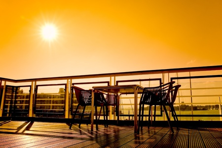 sunsets: silhouette of table and chairs in a waterfront cafe scene Stock Photo