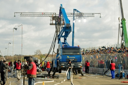 Blackbushe, UK - March 5, 2012: Rain machine and tech crew on the film set of Rush, a motor sport movie directed by Ron Howard