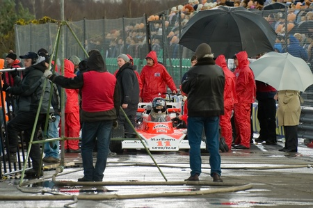 film crew: Blackbushe, UK - March 5, 2012: Actor Chris Hemsworth (as Mclaren F1 driver James Hunt) on the film set of Rush, a motor sport movie directed by Ron Howard Editorial