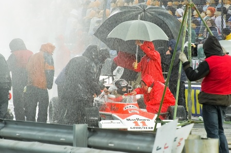 directed: Blackbushe, UK - March 5, 2012: Actor Chris Hemsworth (as Mclaren F1 driver James Hunt) filming rain scenes for Rush, a Formula 1 movie directed by Ron Howard