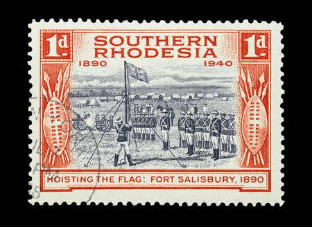 zimbabwe: Sello de correo impreso en Rhodesia del Sur, ahora Zimbabwe con bandera de ceremonia recaudando más de una guarnición militar británica, alrededor de 1940 Editorial