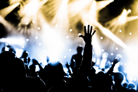 concert crowd: crowd cheering and hands raised at a live music concert Stock Photo