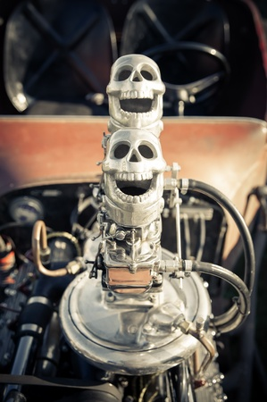 novelty skull carburetor air-intakes on top of a vehicle engine photo