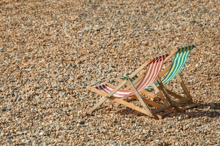 empty deckchairs on a pebbled beach in summer photo