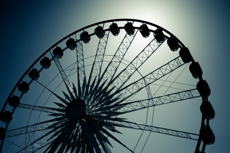 theme park ferris wheel silhouette backlit by moonlight photo