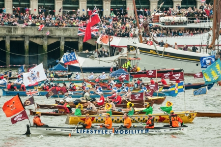 London, UK - June 3, 2012: Colorful flotilla of rowing boats, part of the one thousand boat Queen Elizabeth II Diamond Jubilee Pageant on the River Thames.