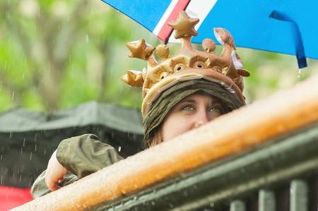 London, UK - June 3, 2012  Beautiful girl in the rain wearing a crown watching the Queen Elizabeth II Diamond Jubilee Pageant on the River Thames