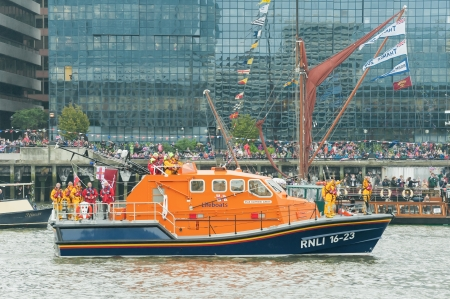 lifeboats: London, UK - June 3, 2012: Crew on-board the RNLB Diamond Jubilee maritime rescue lifeboat, part of the one thousand vessel Queen Elizabeth II Diamond Jubilee Pageant on the River Thames.