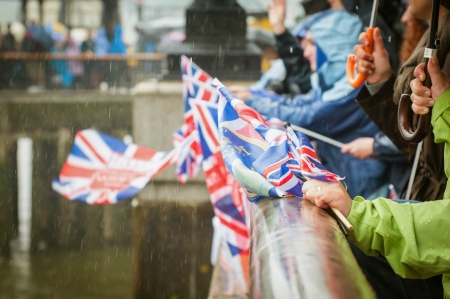 british people in heavy rain celebrating a parade photo
