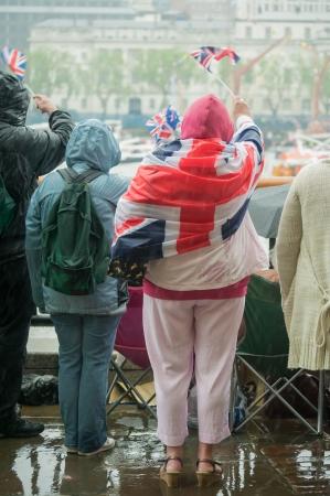 british people in heavy rain celebrating a parade photo