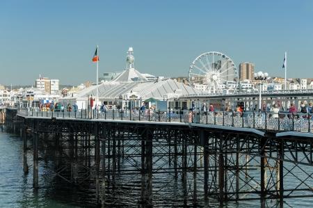brighton beach: Brighton, UK - April 2, 2012: Tourists enjoying the fine weather on the famous landmark of Palace Pier in Brighton seafront.