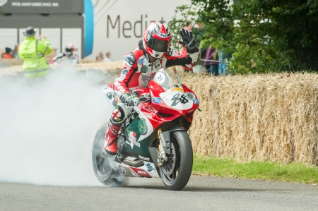 wheelspin: Goodwood, UK - July 1, 2012: One handed burnout by British Superbike rider Scott Smart on the hill course at the Goodwood Festival of Speed, UK Editorial