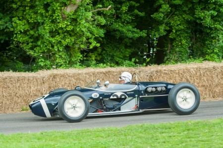 autos: Goodwood, UK - July 1, 2012: Motor-sport legend, Stirling Moss in his classic Lotus 18 Formula 1 car on the hill course at Goodwood, UK