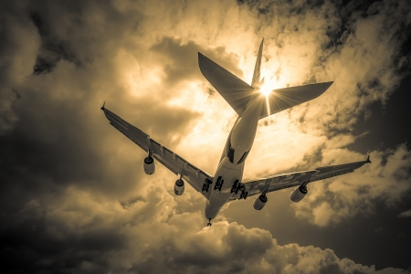 jumbo: abstract of a large passenger jet landing through golden clouds