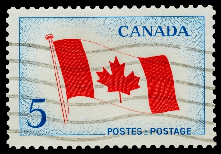 canada stamp: Mail stamp printed in Canada featuring the national maple leaf flag, circa 1965