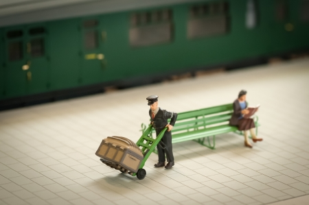 sacktruck: miniature figure of a railway staion porter moving luggage - shallow d.o.f.