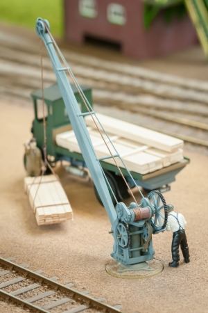wood railroad: miniature figure loading wood with a toy crane