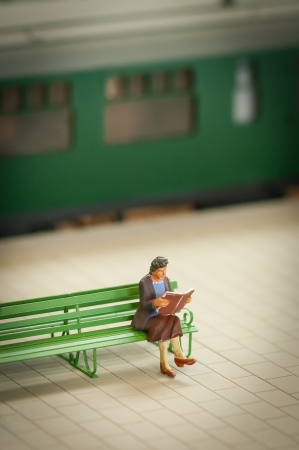 miniature model of a woman reading on a train station platform photo