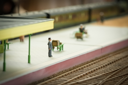 toy train: miniature model of a well dressed man waiting for a train