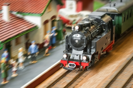 railway station: model railroad steam locomotive (with fake number) speeding through a station Stock Photo