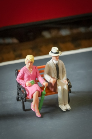 strangers: miniature people seated on a bench on a railway platform