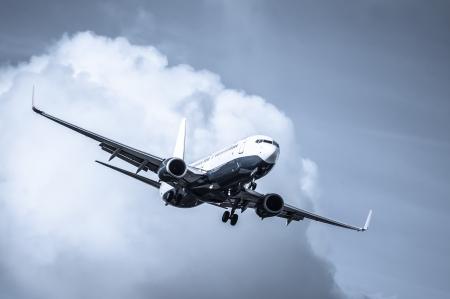cool toned passenger jet on landing approach through a cloudy sky Standard-Bild