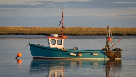 unmarked: small unmarked fishing boat moored in an estuary at sunset