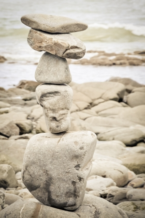 sepia toned stack of balanced rocks on a beach photo