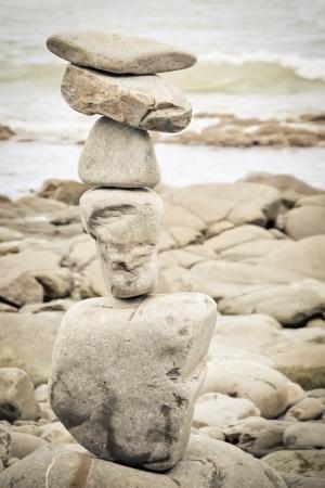balanced rocks: sepia toned stack of balanced rocks on a beach Stock Photo