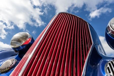 car grill: restored classic car radiator grille closeup against blue sky