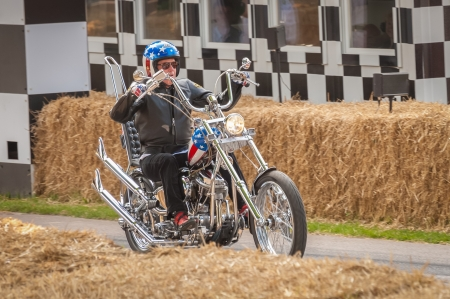 peter: Goodwood, UK - July 13, 2013: Hollywood actor Peter Fonda on a Captain America chopper motorcycle  from the movie, Easy Rider at the Festival of Speed event, held at Goodwood, UK