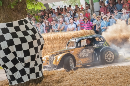 wheelspin: Goodwood, UK - July 13, 2013: Dusty vehicle donuts performed by expert stunt driver Terry Grant at the Festival of Speed event held at Goodwood, UK