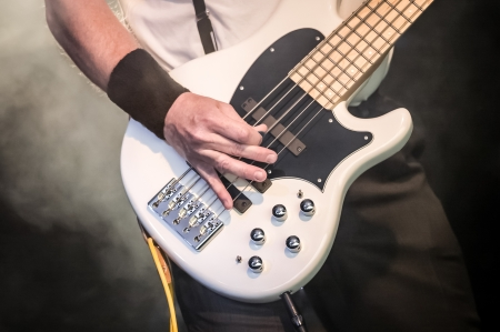 hand of a musician playing a five string bass guitar photo