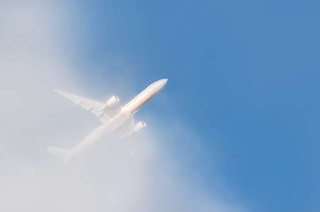 jetset: unmarked passenger jet punching through cloud into blue sky