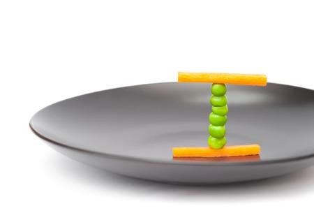 alimentacion equilibrada: concepto de dieta equilibrada de alimentos utilizando los guisantes y las zanahorias en un plato