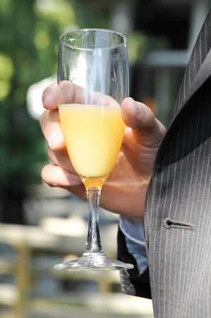 person in suit drinking orange juice and sparkling wine photo