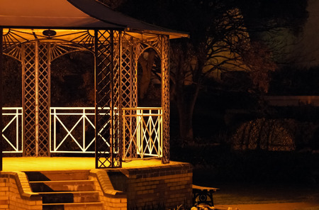 bandstand: empty bandstand stage under faint spotlights Stock Photo