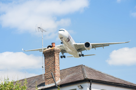 jets: Farnborough, UK - July 14, 2014  Qatar Airways Airbus A350 on landing approach over rooftops to participate at the Farnborough Airshow,  UK
