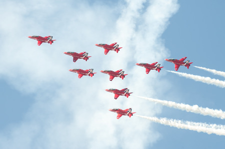 Farnborough, UK - July 18, 2014: The Red Arrows formation aerobatic display team leaving smoke trails in the sky over Farnborough, UK