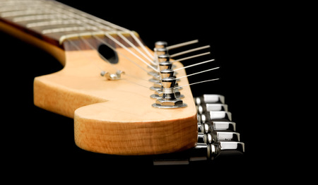 frets: electric guitar neck and strings close-up on black Stock Photo