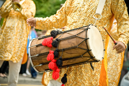 drumming: musician playing a traditional asian dhol drum