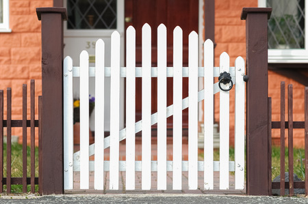 white wooden gate and low fence around a garden