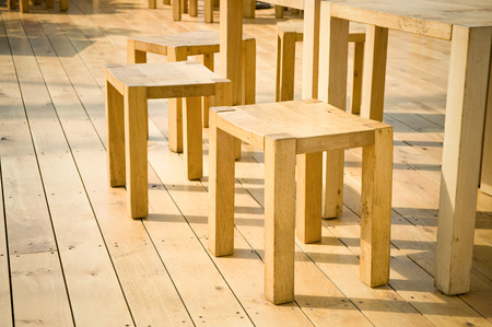 barstool: wooden stools and tables on decking floorboards Stock Photo