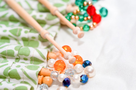white linen: wooden lacemaking bobbins and decorative beads on white linen Stock Photo
