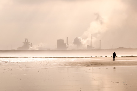 powerstation: sepia toned landscape of a silhouette and power station on a beach