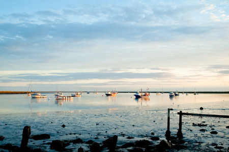 ness: fishing boats moored in a tidal estuary at sunset Stock Photo